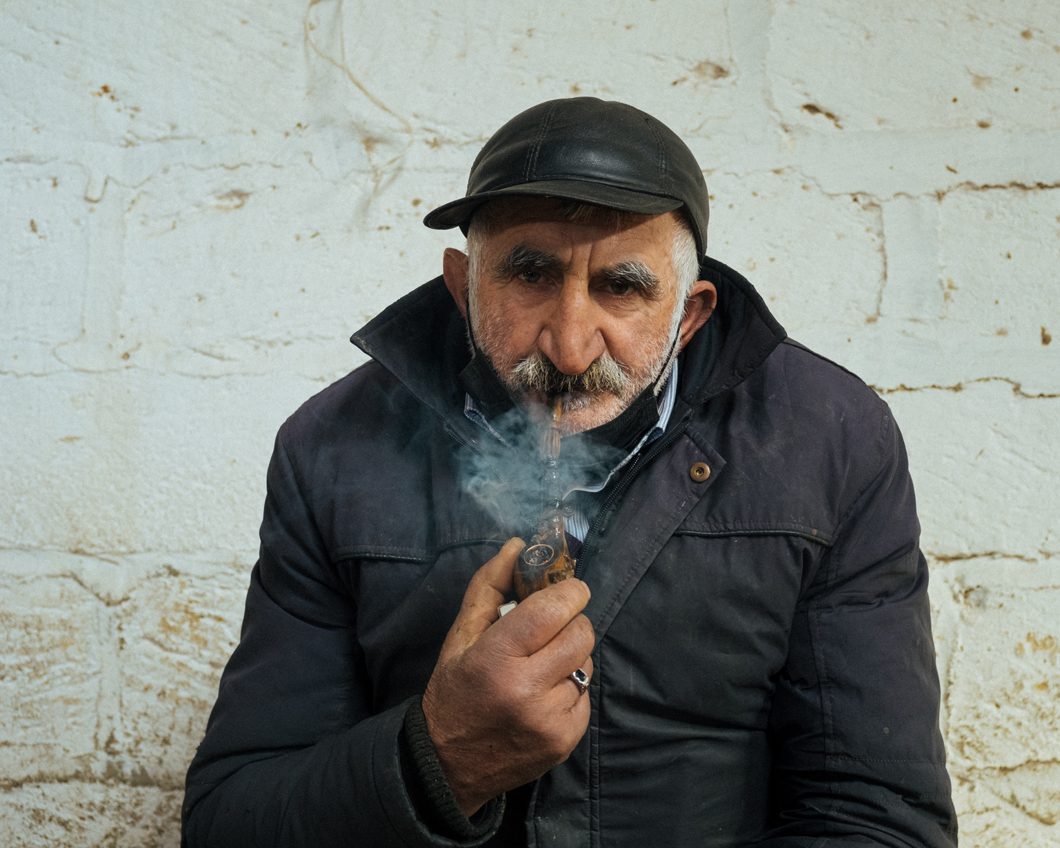 Vagif smokes local tobacco while waiting for buyers. Shaki, 2021