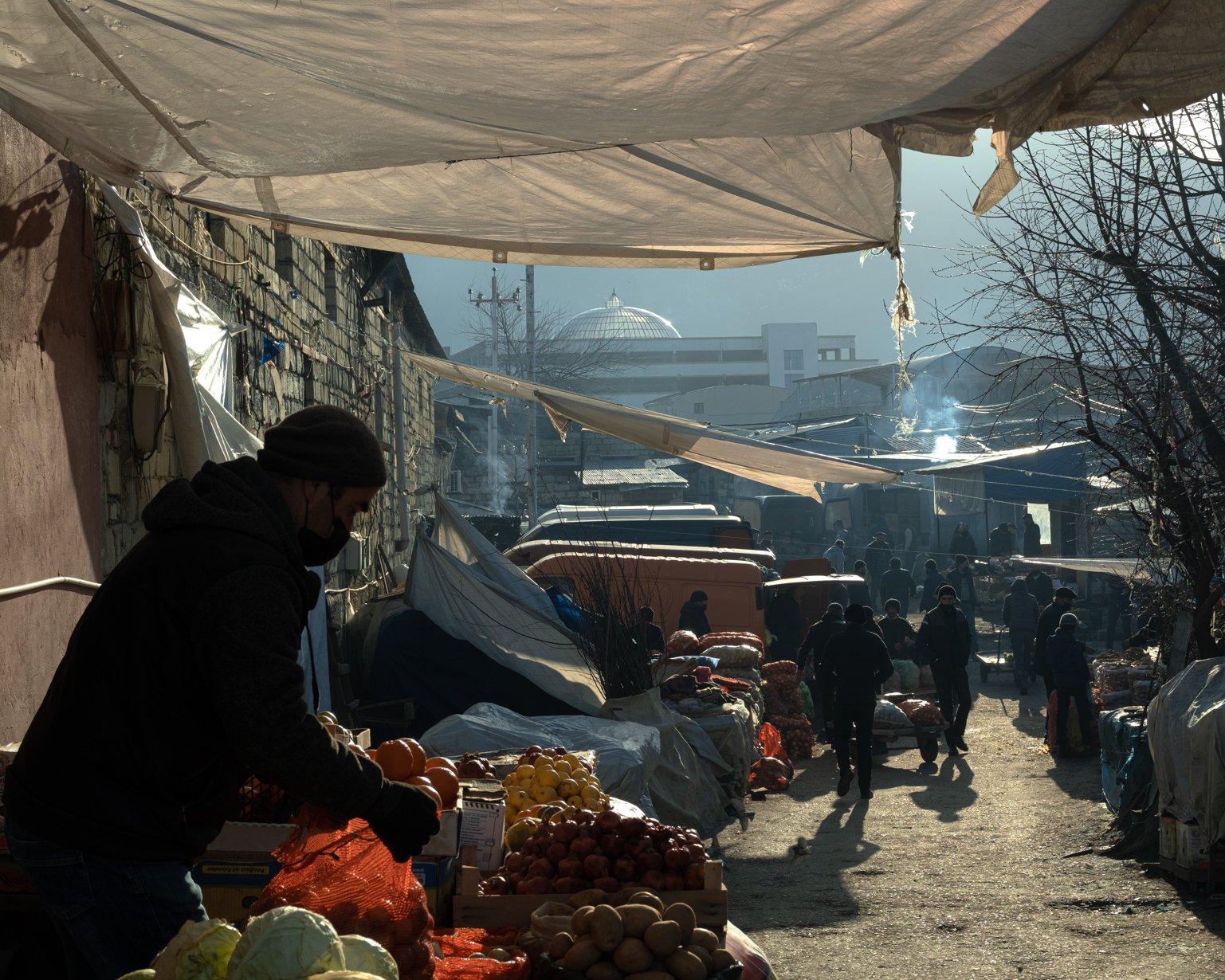 A seller prepares his stand early in the morning near the entrance to Taza Bazaar. Shaki, 2021